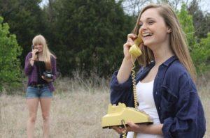固定電話を持ち笑いながら話す女性