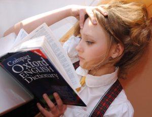 頭を抱えながら書籍を見る女子
