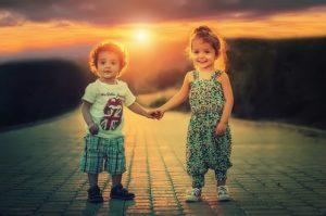 夕日をバックに手を繋ぐ子供