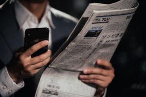 新聞片手にスマホを見る男性