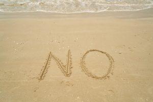 砂浜に書かれたNOの文字