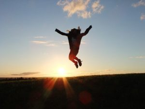 朝日が見える丘で飛び跳ねる女性