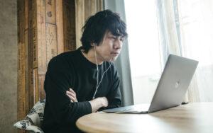 神妙な表情でパソコンを見る男性