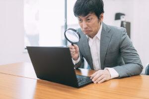 パソコンを虫眼鏡で見る男性